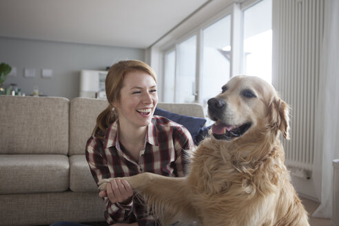 Portrait of smiling young woman holding paw of her dog - RBF003844