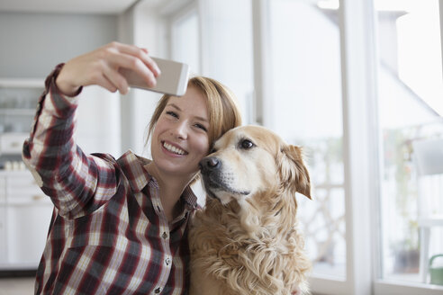 Portrait of smiling young woman taking a selfie with her dog - RBF003847