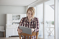 Portrait of smiling young woman using her digital tablet at home - RBF003850