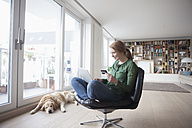 Young woman with credit card and laptop sitting on a leather armchair in her living room - RBF003859