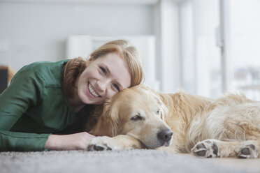 Portrait of smiling young woman lying with her dog on the carpet - RBF003865