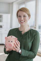 Portrait of smiling young woman with piggy bank - RBF003871