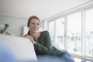 Portrait of smiling young woman sitting on the couch at home - RBF003874