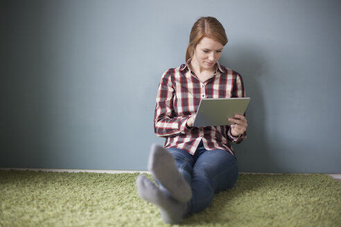Smiling young woman sitting on the floor using digital tablet - RBF003892