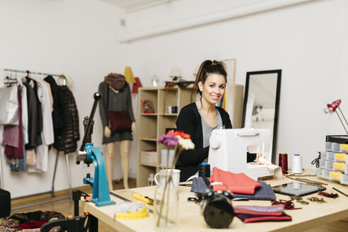 Young fashion designer working in her studio - JRFF000267