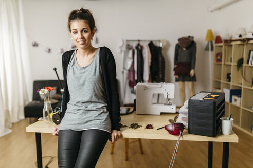 Young fashion designer in her studio, leaning against desk - JRFF000279