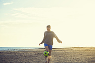 Spain, Young woman playing soccer at the beach - KIJF000079