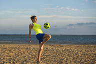 Spain, Young woman playing soccer at the beach - KIJF000082