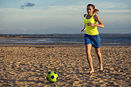 Spain, Young woman playing soccer at the beach - KIJF000085