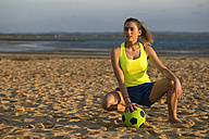 Spain, Young woman playing soccer at the beach - KIJF000088