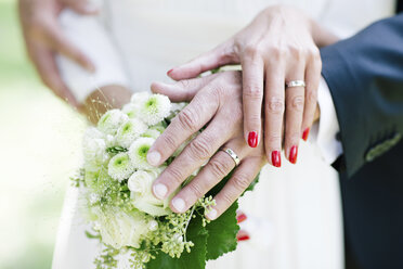 Bride and groom showing wedding rings, holding bouquet - DAW000431