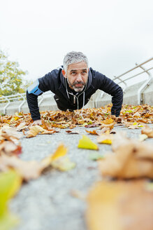 Man doing pushups surrounded by autumn leaves - AIF000163