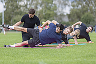 Coach doing exercises with team on sports field - SHKF000382