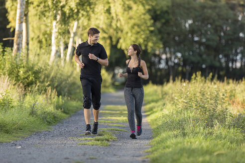 Man and woman jogging on rural path - SHKF000409