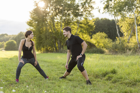 Man and woman stretching in field - SHKF000412