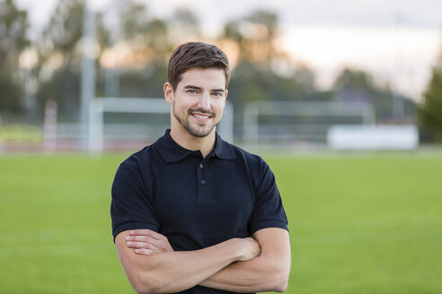 Portrait of smiling man on sports field - SHKF000421