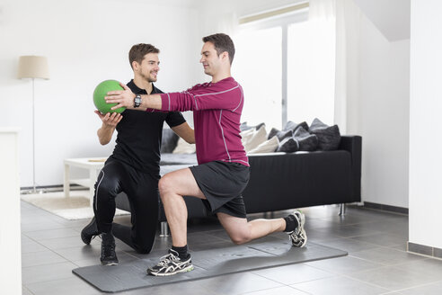 Coach doing exercises with man at home - SHKF000424