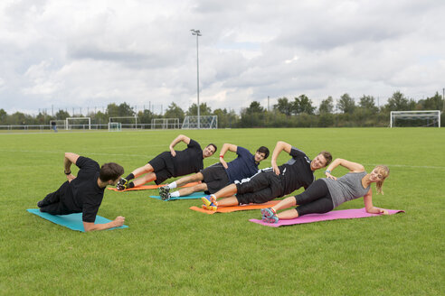 Coach doing exercises with team on sports field - SHKF000430
