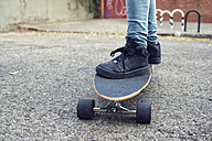 Young woman standing on a  longboard, close-up - KIJF000100