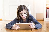 Portrait of girl lying on wooden floor using digital tablet - LVF004375