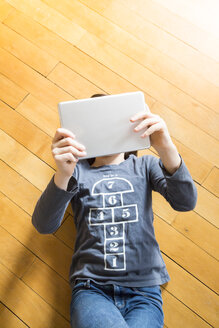 Girl lying on wooden floor covering her face with digital tablet - LVF004378