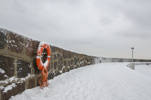 Germany, Sassnitz, life belt on wall in winter - ASCF000442