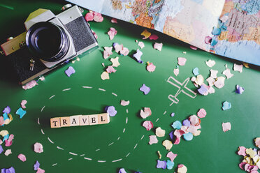 Wooden letters forming the word travel next to a camera with confetti arround - GEM000596
