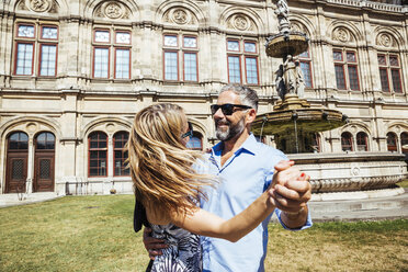 Austria, Vienna, smiling couple dancing Viennese waltz in front of state opera - AIF000165