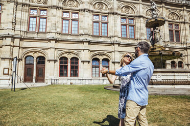 Austria, Vienna, smiling couple dancing Viennese waltz in front of state opera - AIF000168