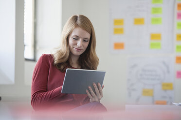 Young woman in office holding digital tablet - RBF003920