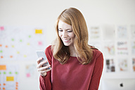 Young woman in office using smartphone - RBF003929