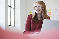 Young woman in office using laptop - RBF003932