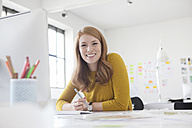 Young woman in office working at desk - RBF003938