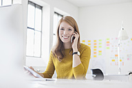 Young woman in office working at desk, using smart phone - RBF003941