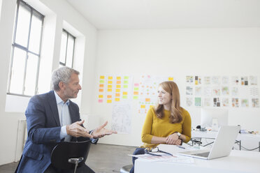 Businessman and coworker discussing in office - RBF003965
