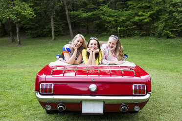 Three happy young women in a convertible parked on e meadow - DAWF000445