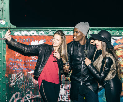 Friends with champagne glasses taking a selfie at graffiti wall at night - OIP000060