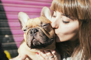 Portrait of young woman kissing French bulldog - GEMF000601