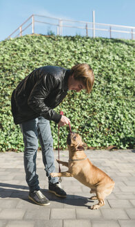 Young man playing with French bulldog - GEMF000604