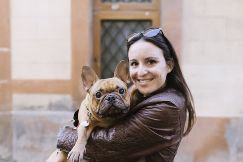 Portrait of French bulldog on the arms of smiling young woman - GEMF000607