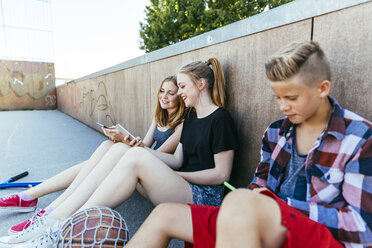 Three teenagers sitting outdoors with smartphones - AIF000169