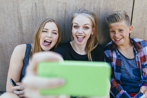 Three playful teenagers outdoors taking a selfie - AIF000175