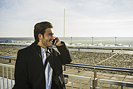 Germany, Frankfurt, Young businessman at the airport using smartphone - UUF006320