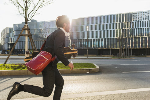 Germany, Frankfurt, Young businessman running with skateboard under his arm, using mobile phone - UUF006341