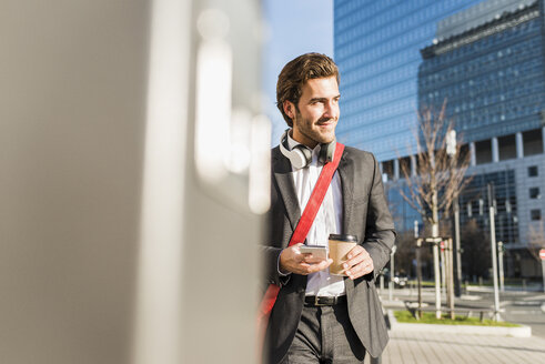 Germany, Frankfurt, Young businessman walking the city with cup of coffee, using mobile phone - UUF006344