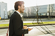 Germany, Frankfurt, Young businessman walking the city with cup of coffee, using mobile phone - UUF006347