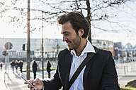 Germany, Frankfurt, Young businessman in the city using mobile phone - UUF006353