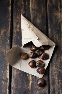 Paper bag with roasted chestnuts on dark wood - CSF026965