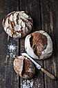 Three crusty breads, bread knife and scattered salt grains on dark wood - CSF026971