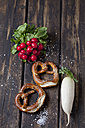 Two pretzels, red radishes, radish and scattered salt grains on dark wood - CSF026986